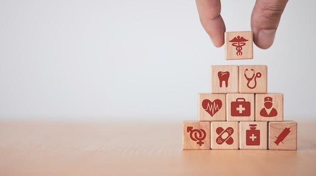 Concetto medico e ospedaliero sanitario, messa a mano e cubetti di blocco di legno che stampano icone sanitarie sullo schermo sul tavolo con spazio di copia.