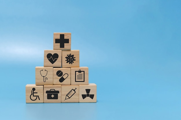 Assistenza sanitaria. icona medica su blocco piramidale di legno cubo pila su sfondo blu con spazio copia, vaccinazione, laboratorio, prevenzione del virus covid-19, salute, tecnologia medica e concetto assicurativo