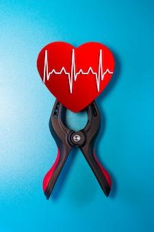 Concetto di sanità e medicina - close up di un cuore rosso con una linea di ecg bloccato in una morsa per la rianimazione. salvezza della vita e dei sentimenti. san valentino.