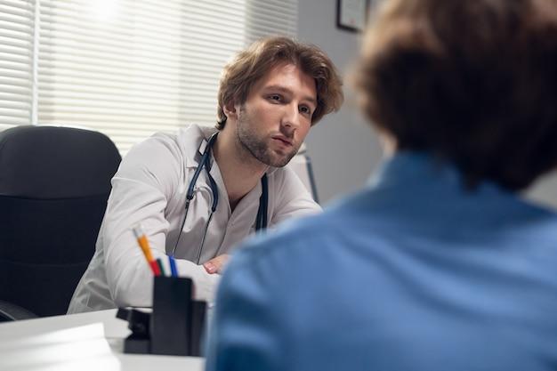 Concetto di sanità e medicina - un medico con il suo paziente in una sala di consultazione.