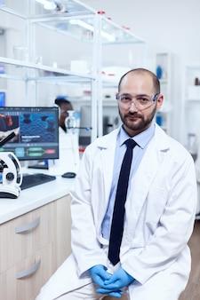 Ricercatore sanitario che indossa camice da laboratorio e occhiali protettivi che guarda l'obbiettivo. esperto serio in genetica in laboratorio con tecnologia moderna per indagini mediche con assistente africano in backg
