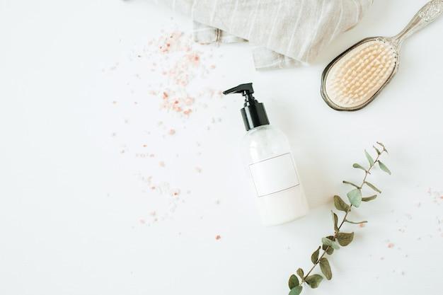 Concetto della stazione termale di sanità con la bottiglia del sapone liquido dello spazio della copia, eucalipto, spazzola per capelli su bianco