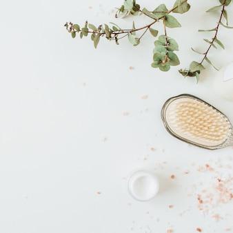 Concetto di spa sanitaria con spazio copia mock up con eucalipto, spazzola per capelli, crema su bianco