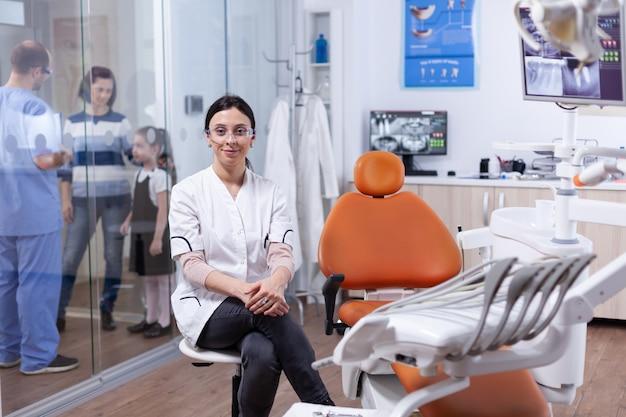 Specialista sanitario in igiene dei denti che indossa camice bianco seduto su uno sgabello e assistente che discute con i pazienti. stomatolog nella clinica dei denti professioanl sorridente indossando l'uniforme che guarda l'obbiettivo.
