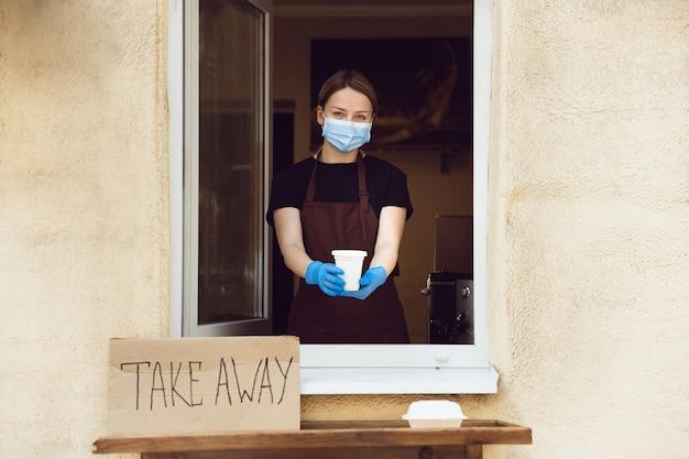 Assistenza sanitaria. donna che prepara bevande e pasti, indossando guanti e maschera protettiva. servizio di consegna senza contatto durante la pandemia di coronavirus in quarantena. porta via solo il concetto. pacchetti riciclabili.