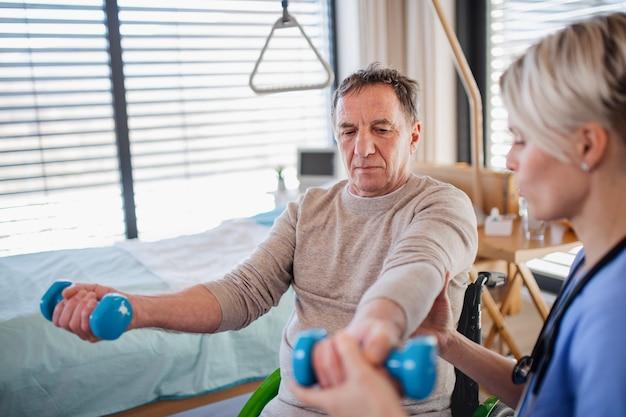 Un operatore sanitario e un paziente anziano in ospedale, concetto di fisioterapia.