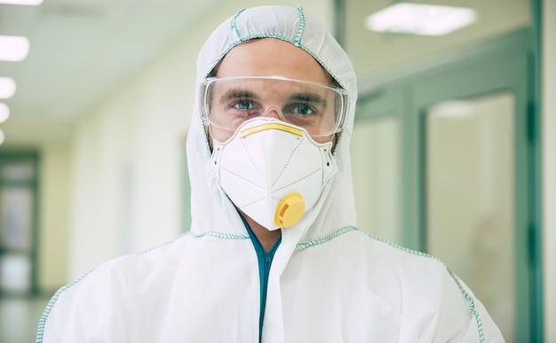 Operatore sanitario che indossa una tuta dpi per lavorare in ospedale durante la pandemia covid-19. dottore in costume di sicurezza