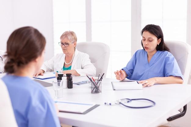 Operatori sanitari che hanno una riunione nella sala conferenze dell'ospedale. terapeuta esperto della clinica che parla con i colleghi della malattia, professionista della medicina