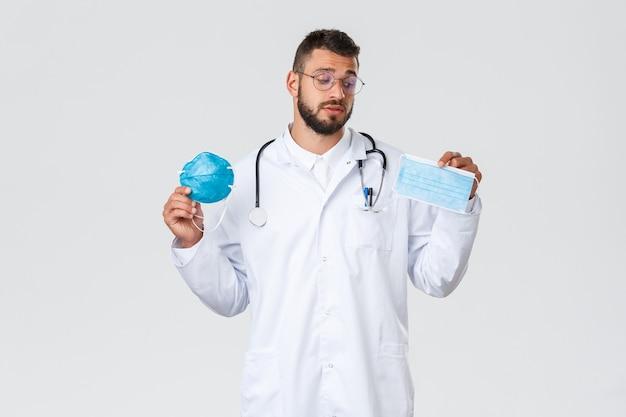 Operatori sanitari, assicurazione medica, concetto di pandemia e covid-19. medico maschio indeciso in camice bianco e occhiali, guarda indeciso la maschera medica, mostrando il respiratore dpi.