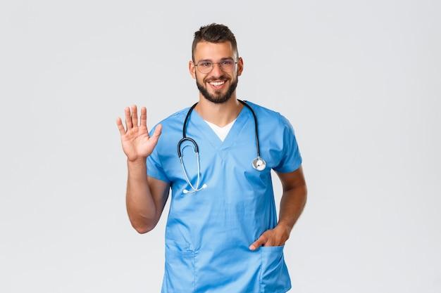 Operatori sanitari, medicina, covid-19 e concetto di auto-quarantena pandemica. amichevole dottore allegro, infermiere in camice e occhiali, agitando la mano per salutare, salutando i pazienti in clinica.