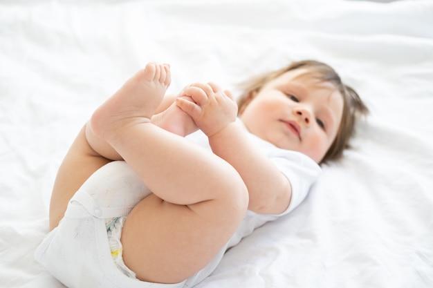 Un neonato di 6 mesi in buona salute che sorride e che si trova su una biancheria da letto bianca a casa. messa a fuoco selettiva sulle gambe.
