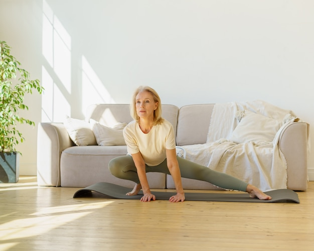 Donna in pensione attiva e sana in abiti sportivi che fa esercizi di stretching sul tappetino da yoga in soggiorno