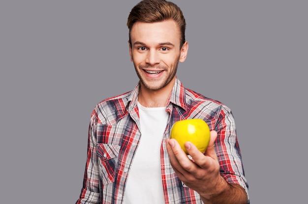 Alternativa sana. uomo sorridente che tiene la mela verde di fronte a lui mentre sta in piedi su uno sfondo grigio
