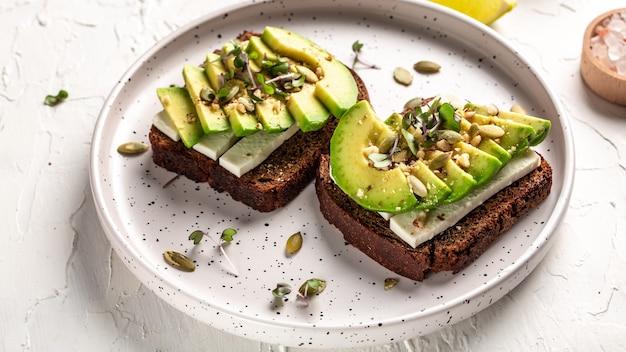 Salutari toast di avocado per colazione o pranzo con pane di segale, avocado a fette, formaggio, zucca e semi di sesamo