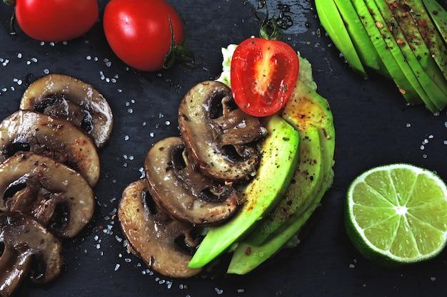 Toast avocado sani con funghi e pomodorini.