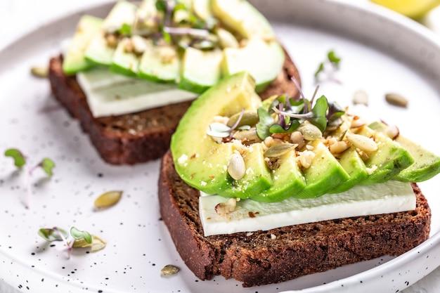 Salutari toast di avocado con pane di segale, avocado a fette, formaggio, zucca, noci e sesamo per colazione o pranzo