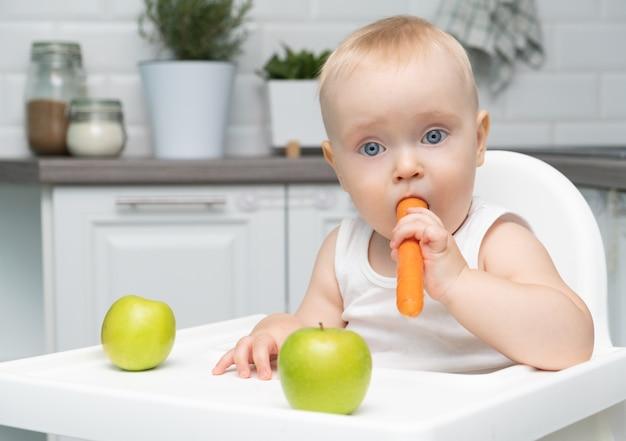 Neonato in buona salute che si siede sulla sedia di un bambino in cucina e mangia la carota arancione.