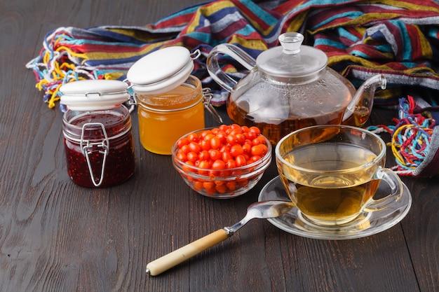 Sfondo sano. marmellata di bacche selvatiche e lampone, miele e tè sulla tavola di legno di caduta