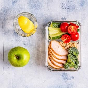 Lunch box sano ed equilibrato con pollo, riso, verdure. cibo per ufficio, concetto di stile di vita sano.