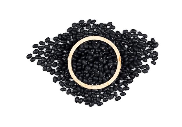 Fagioli neri sani in una tazza di legno su sfondo bianco