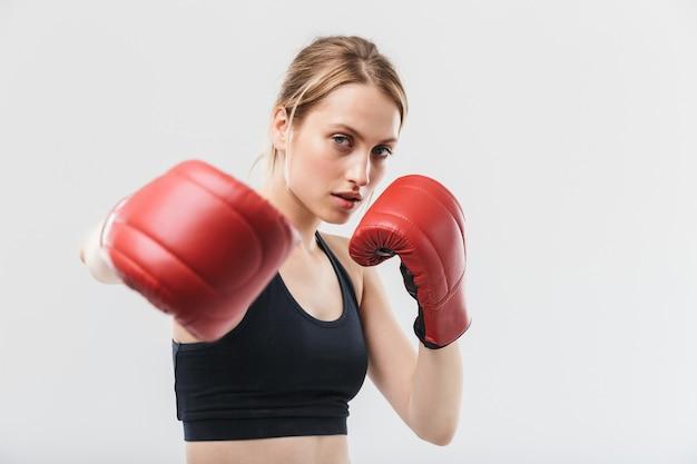 Donna bionda in buona salute vestita con abbigliamento sportivo e guantoni da boxe che si allenano e durante il fitness in palestra isolato su muro bianco