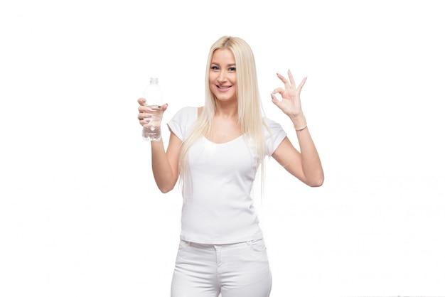 Donna bionda in buona salute che tiene e che beve vetro e bottlle di acqua pura su fondo bianco isolato