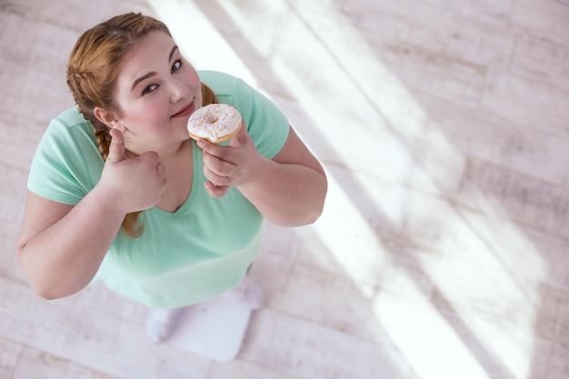 Corpo sano. donna grassoccia dai capelli rossi che mostra il buon esempio mentre rifiuta il cibo malsano