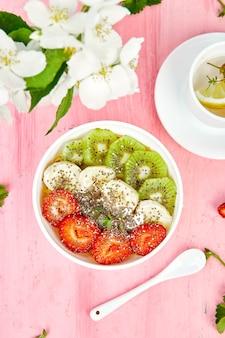 Frullato di ciotola sana colazione con semi di fragola, banana, kiwi e chia.
