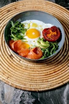 Ciotola sana colazione con uova fritte, salmone, avocado, pomodoro grigliato e insalata che serve con pane sul tovagliolo di paglia
