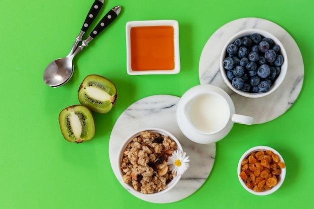 Tavole di salumi per una sana colazione - muesli, yogurt, varietà di frutta e bacche, noci e fiocchi sullo sfondo luminoso dell'estate