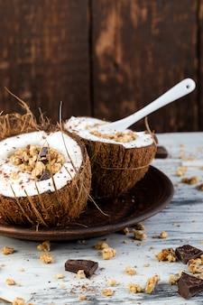 Prima colazione sana in fiocco di cocco su superficie bianca. yogurt in ciotola di cocco con scaglie di cocco, cioccolato e muesli. vista dall'alto, piatto, sopraelevato