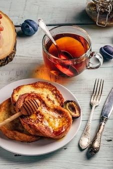 Concetto di colazione sana. toast alla francese con miele, frutta e tè su fondo di legno bianco
