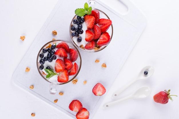 Sana colazione in una tazza con muesli al forno fatti in casa, frutti di bosco freschi e yogurt su uno sfondo bianco da tavola