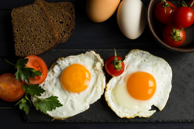 Colazione salutare. uova fritte, verdure e pane. vista dall'alto.