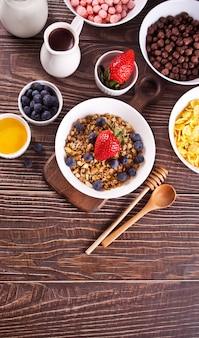 Colazione salutare. muesli, muesli con frutti di bosco freschi e altri fiocchi e palline di mais sullo sfondo. vista dall'alto.