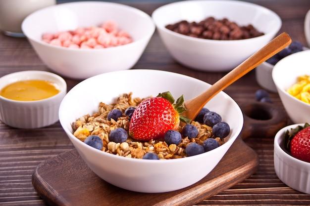 Colazione salutare. muesli, muesli con frutti di bosco freschi e altri fiocchi e palline di mais sullo sfondo.