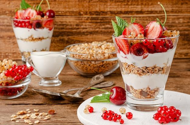 Sana colazione a base di muesli con frutti di bosco e yogurt su uno spazio di legno. copia spazio