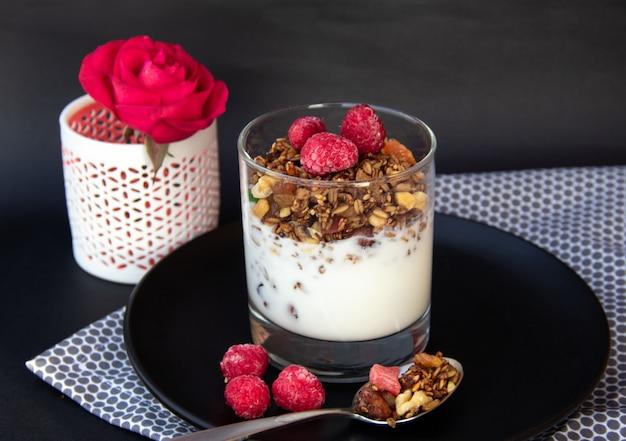 Colazione salutare. muesli con yogurt e lamponi sul piatto nero.