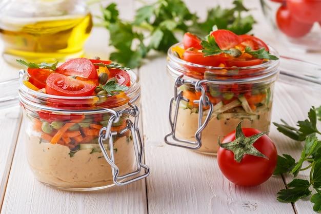 Sana colazione - hummus con verdure in barattoli di vetro.