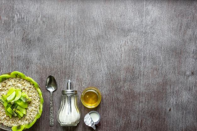 Una sana colazione ingredienti ciotola di avena muesli frutta fresca e miele vista dall'alto spazio copia