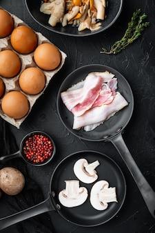 Una sana colazione ingredienti per uova fritte impostato, sulla tavola nera, vista dall'alto laici piatta