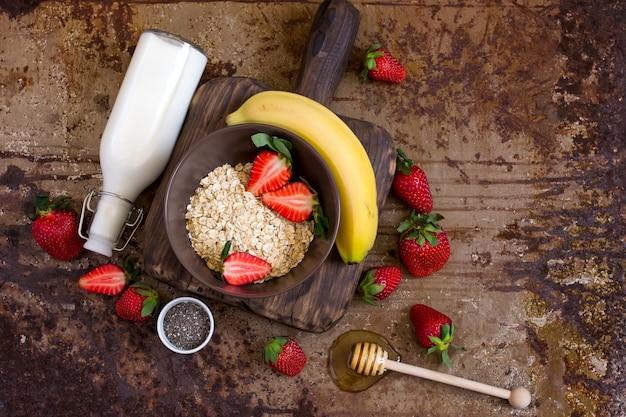 Ingredienti salutari per la colazione: farina d'avena, miele, frutta, fragola e semi di chia. concetto di cibo biologico naturale con. vista dall'alto con copia spazio