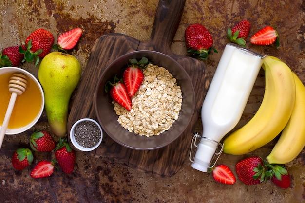 Ingredienti salutari per la colazione: farina d'avena, miele, frutta, fragola e semi di chia. vista dall'alto. concetto di cibo biologico naturale