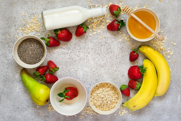 Ingredienti salutari per la colazione: farina d'avena, miele, frutta, fragola e semi di chia. vista dall'alto con spazio per le copie. concetto di cibo biologico naturale.