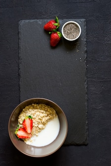 Ingredienti salutari per la colazione: farina d'avena, miele, fragola e semi di chia sul tagliere. vista dall'alto con spazio per le copie. concetto di cibo biologico naturale.