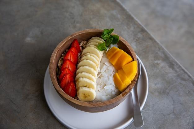 Una sana colazione fatta di una ciotola di frullato in una ciotola di legno con frutta fresca