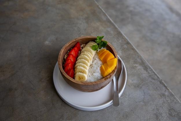 Sana colazione fatta di una ciotola di frullato in una ciotola di legno con frutta fresca