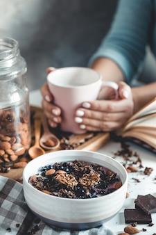 Sana colazione, muesli con frutti di bosco e succo d'arancia servito su un tavolo di vetro e libri. manicure