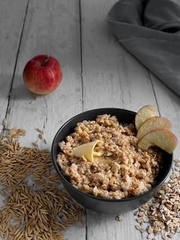 Colazione salutare. farina d'avena con fette di mela e burro. tazza nera con porridge su una tavola di legno bianca. i chicchi di avena sono sparsi sul tavolo. avvicinamento.