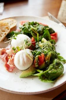 Colazione salutare. uova in camicia, insalata di bistecca con pancetta, rucola, pomodoro e avocado. luce del sole del mattino